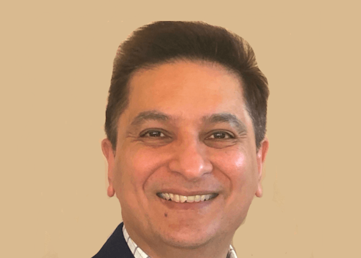 Dhaval Vasavada of Modern Hire is smiling into the camera against a beige background.