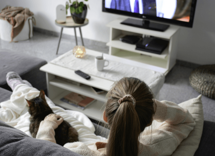 A woman sitting on a sofa wearing pyjamas with a cat on her lap watches Netflix on a television.