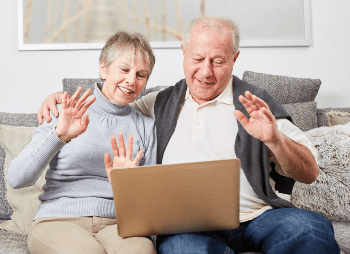 An elderly man and woman sitting on a sofa using a laptop together.