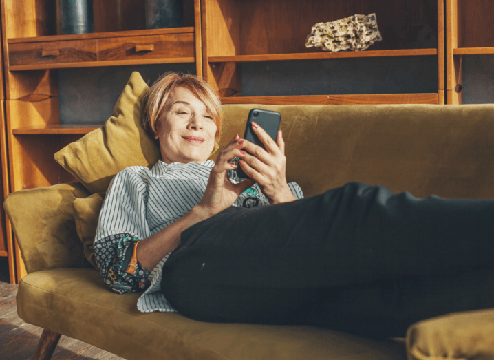 A woman lying on a sofa using a mobile phone and smiling.