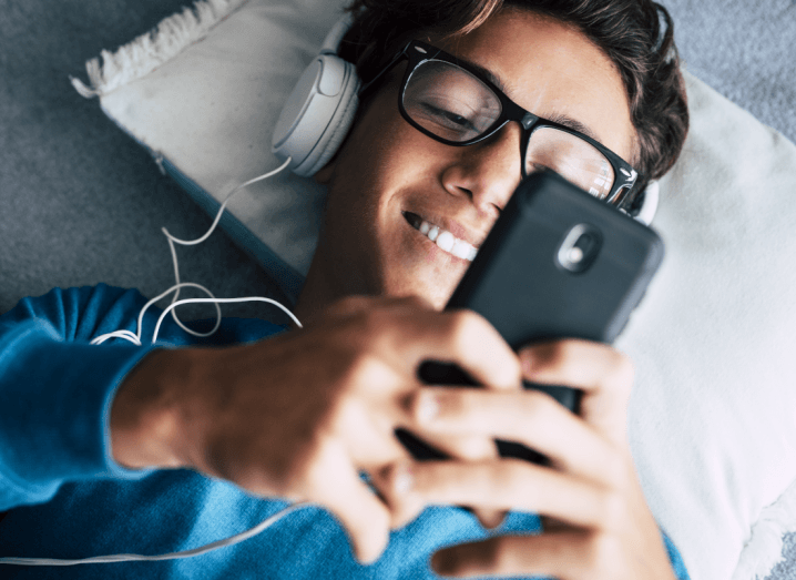 A young man looking at his phone while lying on the ground with a pillow under his head. He is smiling at the phone and wearing white headphones.