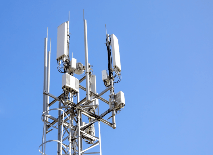 A white 5G phone mast in front of a blue sky.