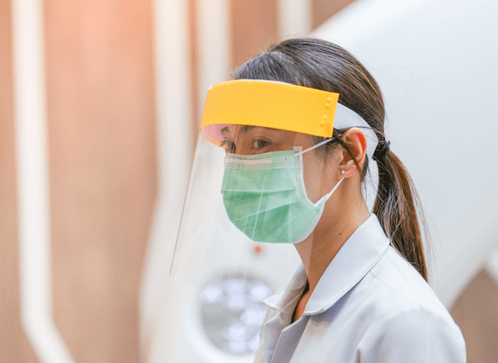 A person wearing a plastic protective mask and a surgical mask with a white surgical coat.