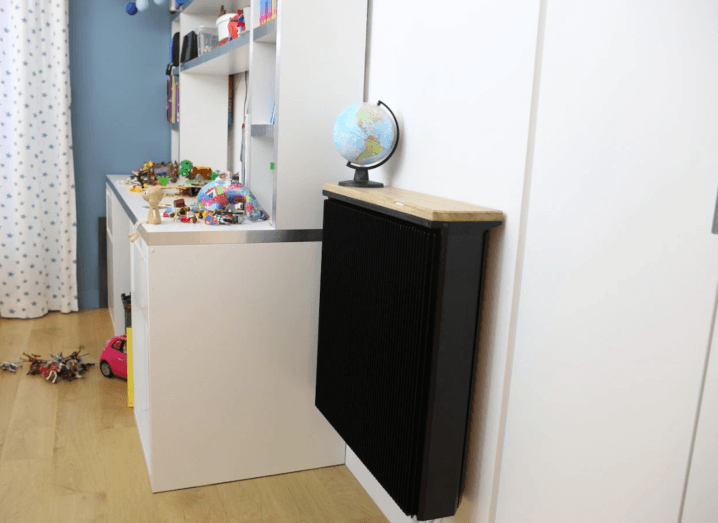 A black radiator mounted to a wall in a child's bedroom beside a desk. There are toys all over the desk and floor.