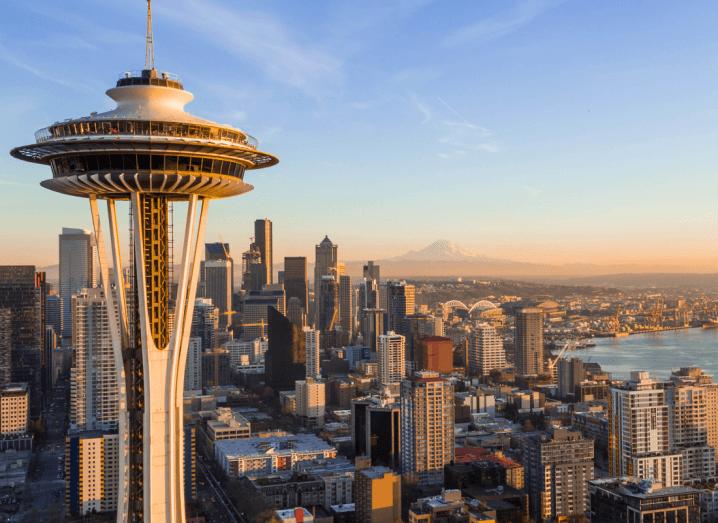 Skyscrapers in Seattle beside a body of water, under a blue sky.