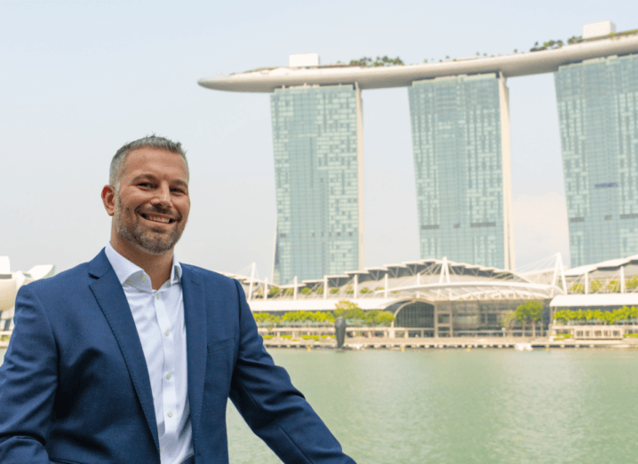A man wearing a navy suit smiling in front of the famous Marina Bay Sands building in Singapore.