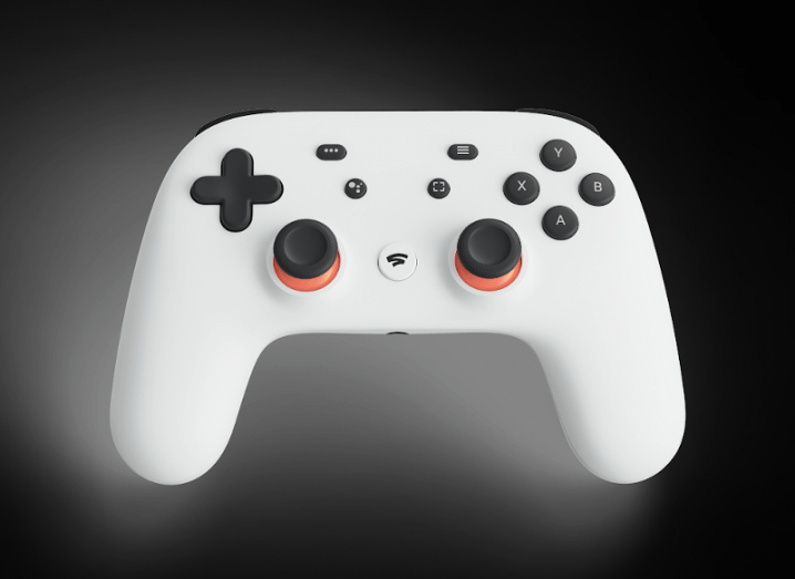 A white Stadia controller in front of a black background.