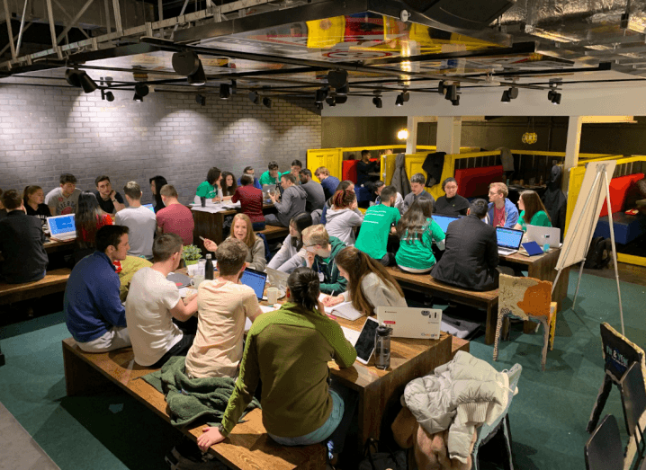 A large group of people sitting together in a colourful room at long tables working together.
