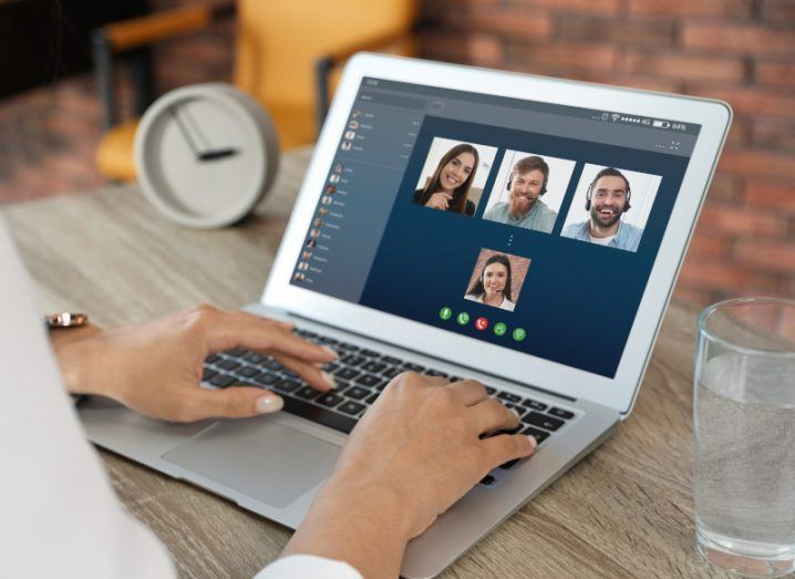 A close-up of a laptop on a desk with four faces on the screen to represent video conferencing.