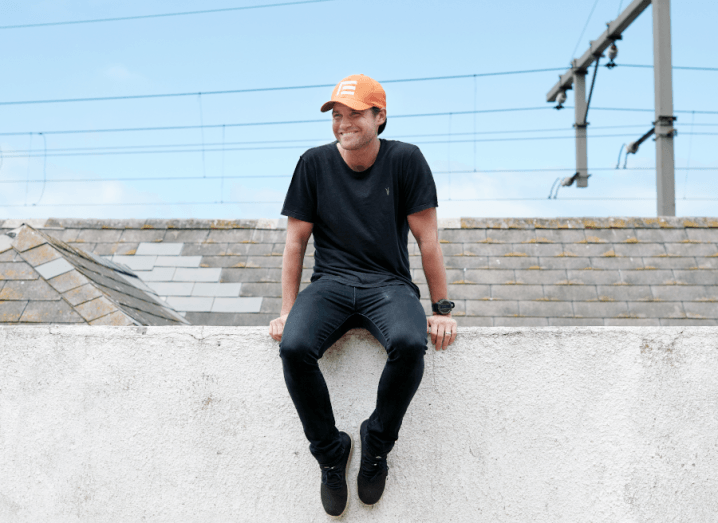 A man wearing denim jeans, a black T-shirt and an orange cap sits on a white wall in front of a blue sky.