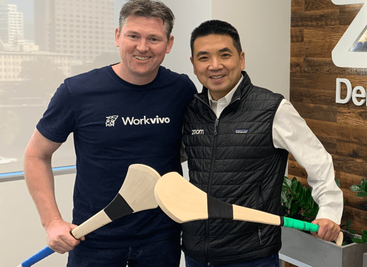Two men standing in an office, holding hurley sticks. One man is wearing a navy Workvivo t-shirt and the other man is wearing a black Zoom gilet.
