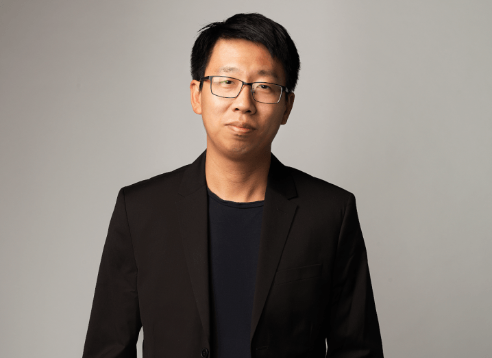 A man with black hair wearing glasses and a black suit.