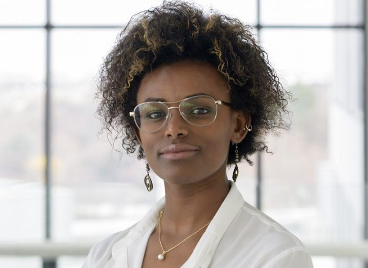 Abeba Birhane in glasses and a white top against a glass building interior.