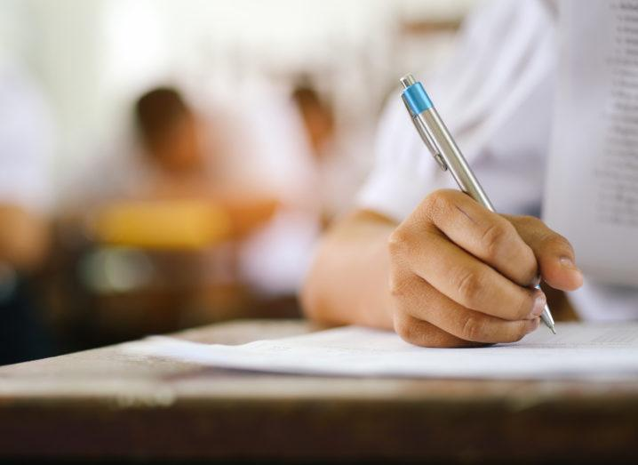 Close-up image of student in a uniform taking a test, writing answers on a piece of paper.
