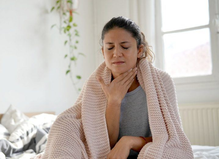 Woman wearing a blanket around her shoulders while holding her throat with a grimaced look.
