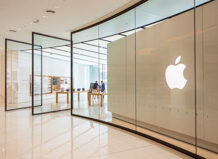 An Apple store with large windows and the Apple logo on a wall.
