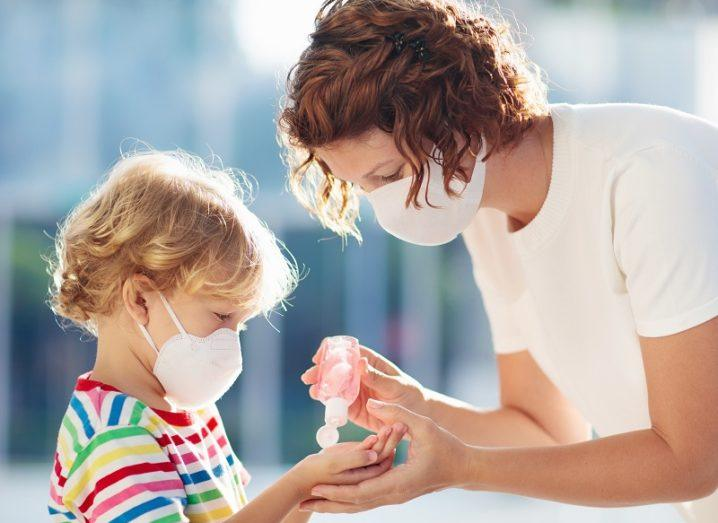 Woman with a face mask giving hand sanitiser to a child, also wearing a mask.