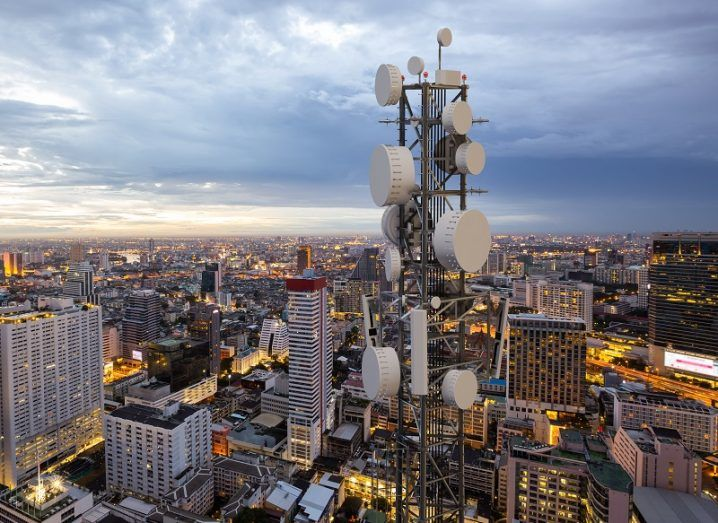 5G tower overlooking a cityscape at dusk.