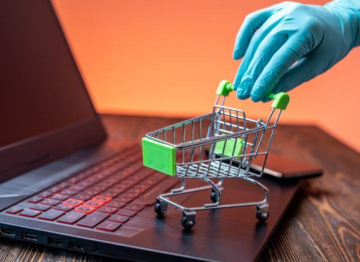 Hand wearing a blue surgical glove pushing a small trolley on a laptop.