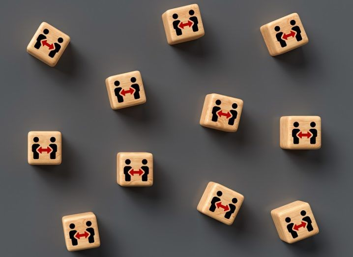 A number of separated wooden blocks with drawings of social distancing between two people on them.