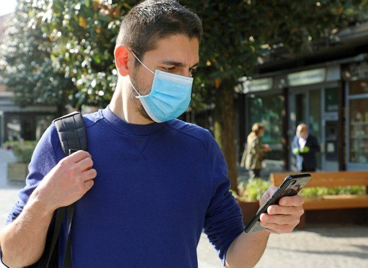Man in a blue jumper wearing a face mask looking at his phone in a public place.