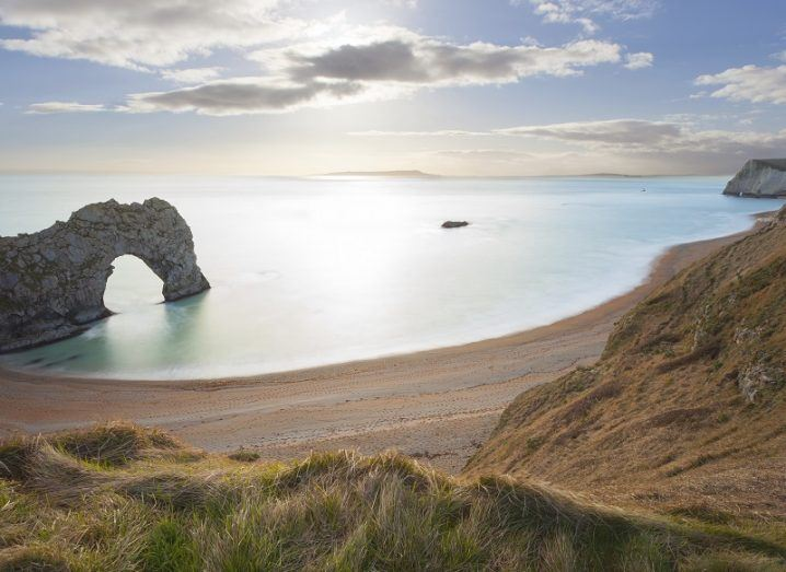 Sunny day at Durdle Door, Dorset with a rock formation jutting out into the sea.