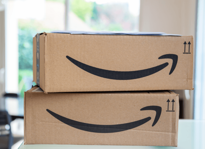 Two brown cardboard Amazon boxes stacked up in a bright room.