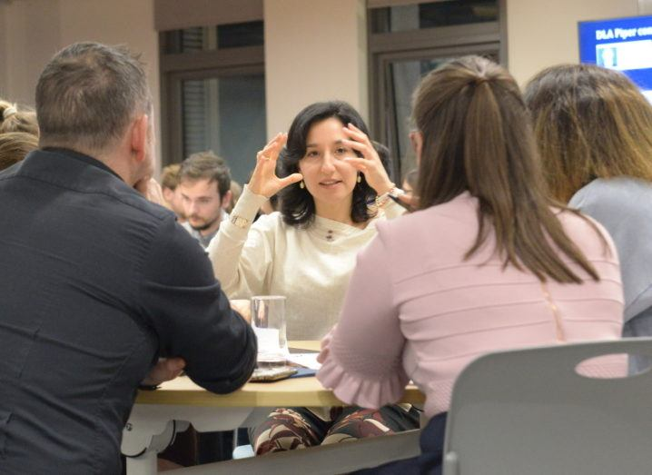 Alessandra Sala gestures with her hands while speaking to a round table of people at a Women in AI event.