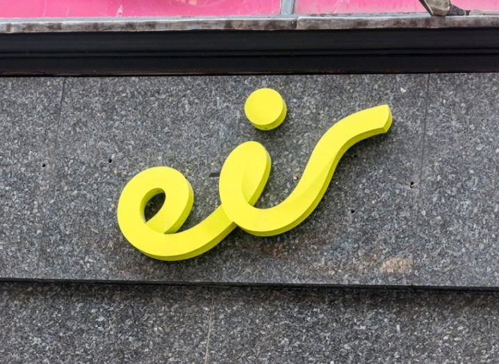 Eir's logo coloured yellow on a grey stone wall.
