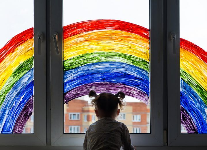 A little girl looks out a window that is painted with a rainbow.