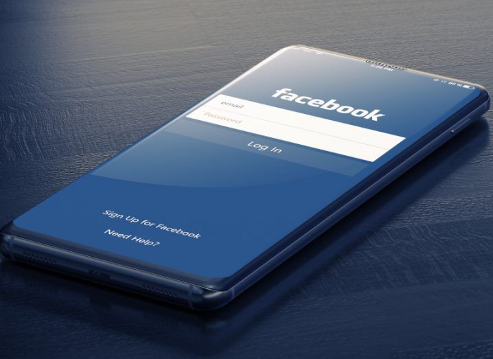 The Facebook loading page on a mobile, which is lying on a dark navy wooden surface.