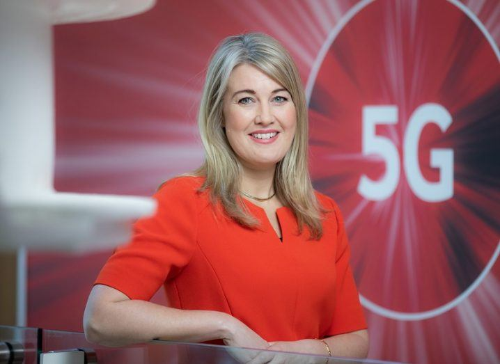 Fiona Sheridan in a red dress smiling and posing in front of a wall with a 5G symbol on it.