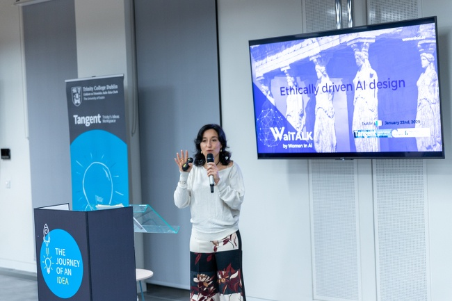 Alessandra Sala holds a microphone and speaks in front of a screen for a women in AI event at Trinity Business School