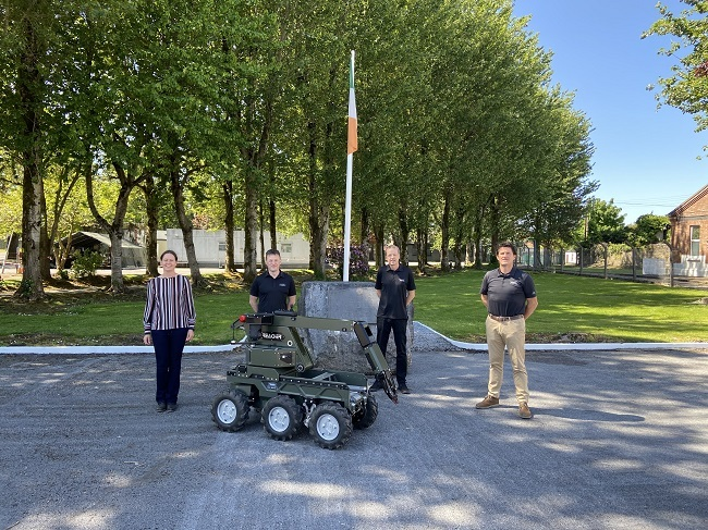 Julie Behan and the Reamda team delivering the Reacher robot to the Irish Defence Forces, with the robot in the foreground.