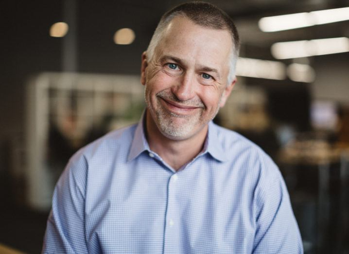 Joe Tobolski of Nerdery is smiling into the camera in a modern corporate space.