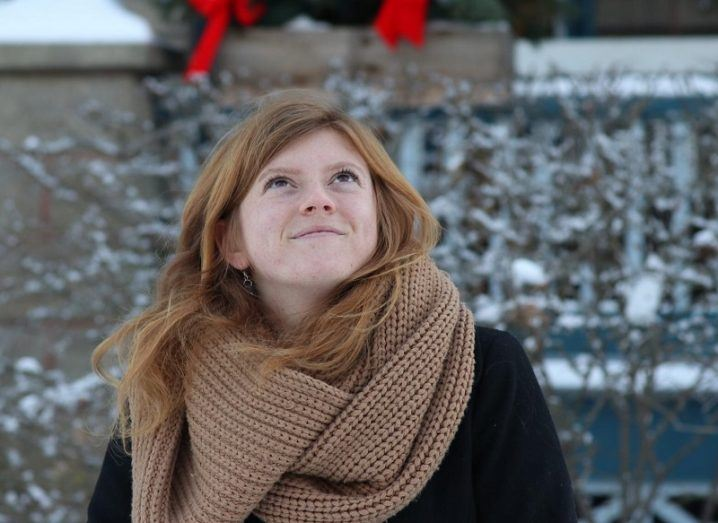 Katie Burns looking up and smiling in a brown scarf and black jacket against a snowy background.