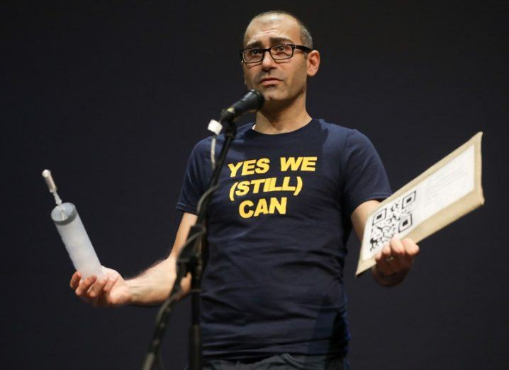 Dr Luca Mirimin holding props on stage while speaking into a microphone against a black background.