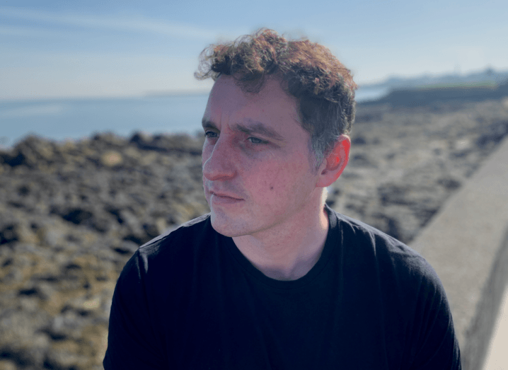 A man with brown, curly hair wearing a navy T-shirt, sitting on a wall in front of a rocky shoreline.