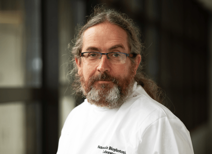 A man with long hair and a beard wearing glasses and a white lab coat.