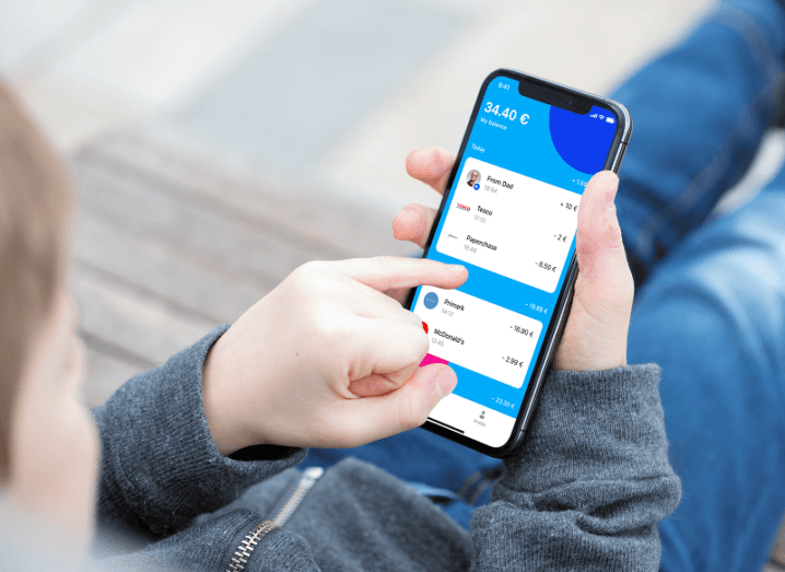 Child's hand using the Revolut Junior app on a smartphone.