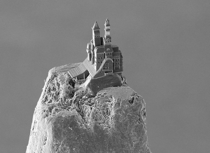 Black and white image of a 3D-printed castle on top of a pencil point.