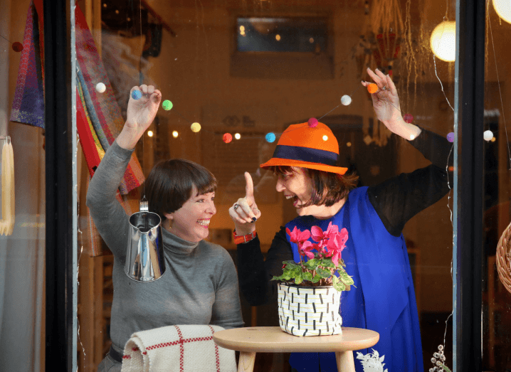Two women in the window of a shop. One is wearing a grey jumper and the other is wearing a blue dress over a black jumper, with an orange hat.