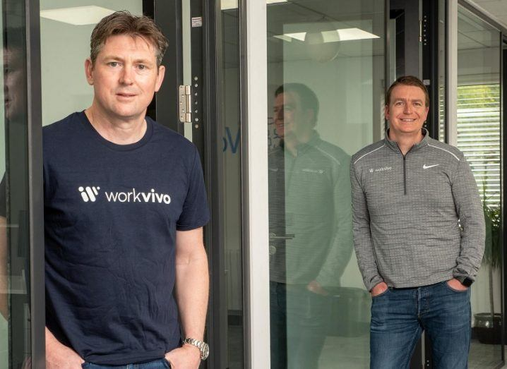 John Goulding and Joe Lennon standing and smiling in the Workvivo office.