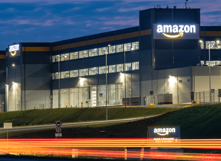 An Amazon warehouse lit up at dusk.