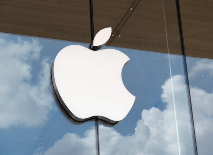 The Apple logo displayed on a window, where clouds are reflected.