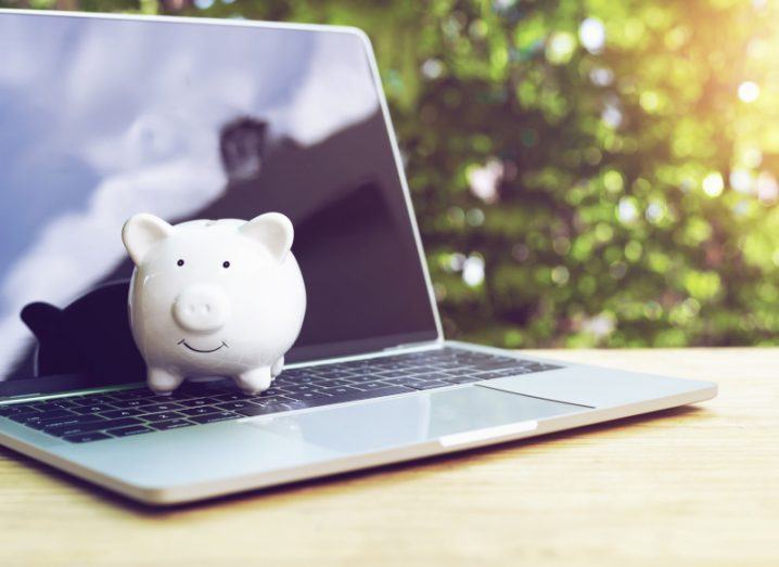 A white piggy bank sits on an open laptop on a table with trees in the background.