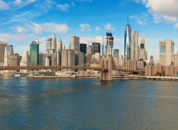 The skyline of New York City in front of a body of water with a large bridge going across the water.
