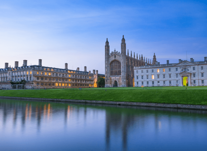 An old university building in front of a river and a patch of grass.