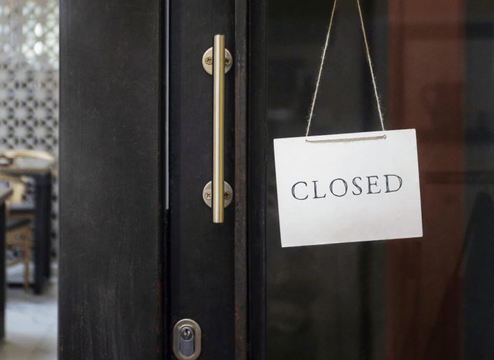 A business with a sign on the door saying it is closed.