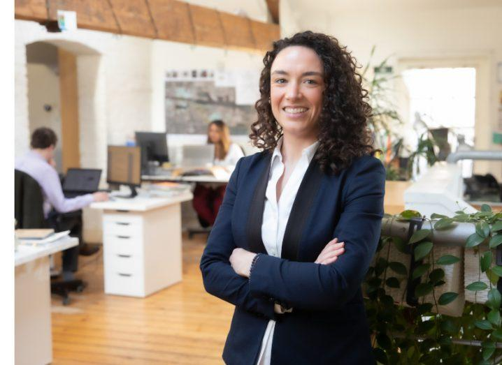 A woman in a dark suit stands with her arms crossed in a bright office space.